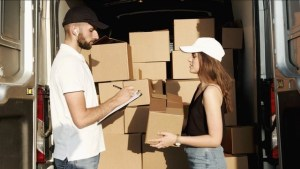 Two people talking in front of the moving truck