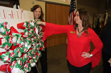 """Tonya Smikal struggled to punch through the paper to get the prize in a """"Naughty or Nice"""" game at the Dayton Chamber luncheon on Dec. 4. In the end, she picked the wrong cup - putting her hand into a naughty cup."""