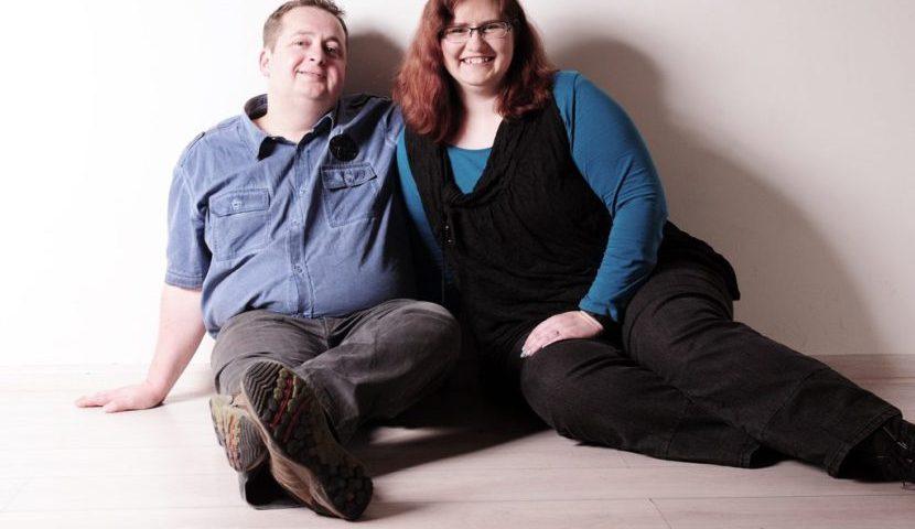 ein Paar sitzt auf dem Boden, die Körper an die Wand gelehnt