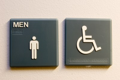 The Men's and Wheelchair sign on the entrance to the restroom.