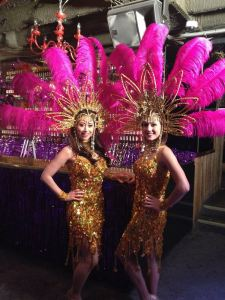 Showgirls in gold with pink headdress