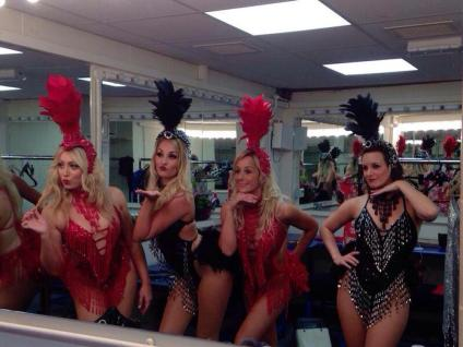 Showgirls posing in a mirror