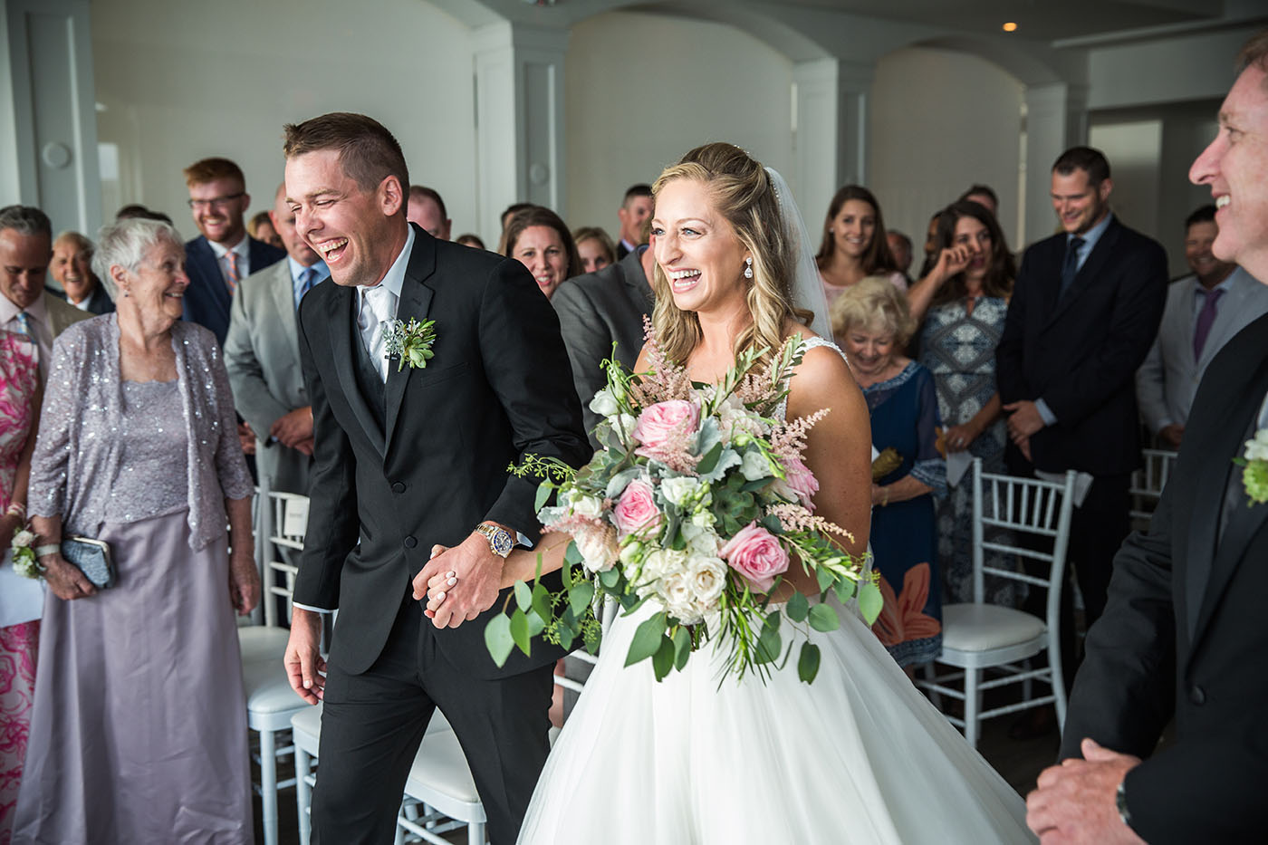 Bride and groom laughing while leaving ceremony