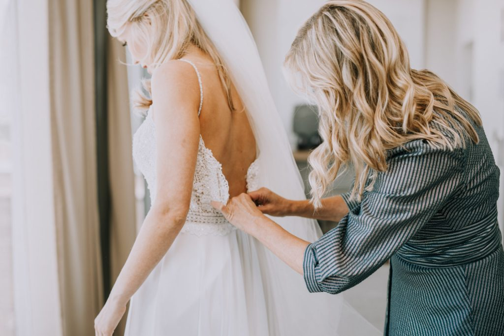 Sasha and Michael | Bride's dress being buttoned up by mother of the bride
