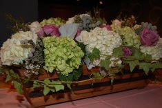 Each table had a hand painted box with white and green hydrangea, cool water and ivory roses, brunia, dusty miller, spider mums, ivy, and thistle.