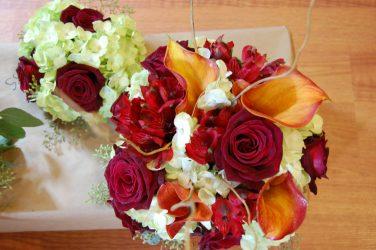 Brides bouquet with mango calla lily, black magic roses, curly willow, alstromeria, and green hydrangea.