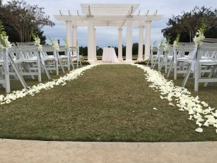 All white ceremony decor with white petals and white orchid aisle markers