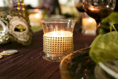 Stunning linens, detailed candles, masks and china for Mardi Gras table