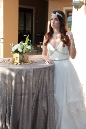 Bride by cocktail table with white floral and gold accents