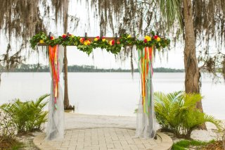 Bright ceremony arch with floral, garland, draping and ribbons