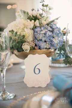 Gold footed bowl with blue hydra, eucalyptus, white hydrangea, blush spray rose and acacia
