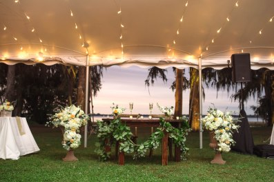 Re-purposed the entrance pieces next to the Sweetheart Table and designed a thick and airy greens garland to drape across their table.