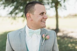 Our handsome Groom wearing a Coral Spray Rose and Dusty Miller boutonniere.