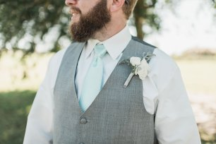 Groomsmen wearing a White Spray Rose and Dusty Miller filled boutonniere.