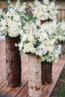 Ceremony set for a queen with log stumps and overflowing white and green floral