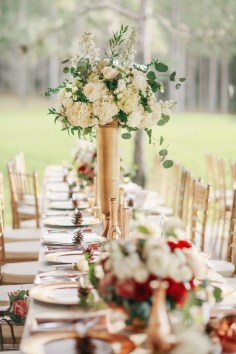 tall, medium and short centerpieces flowing down 24' of family style tables in varying gold containers