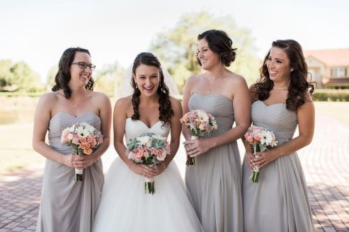 Our Bride and her Maids' enjoying a moment together. The Maids' taupe gowns really compliment the pops of peach Spray Roses and white Gerber Daisies in their bouquets.