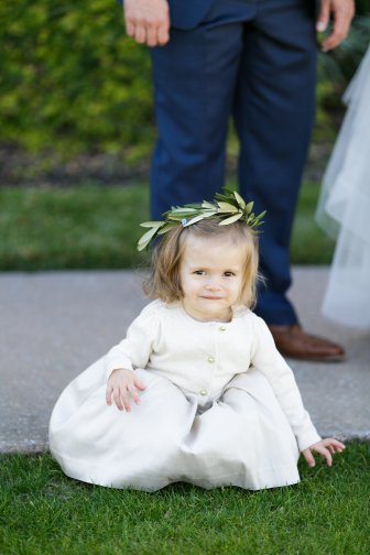 An adorable Flower Girl with an Olive Branch-filled flower crown.