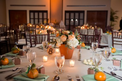 Ceramic Pot centerpieces filled with White Hydrangea, Orange Ranunculus, Seeded Euch, and Peach Hypericum Berry.