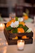 Orange Crate centerpieces filled with White Hydrangea, Orange Ranunculus, Seeded Euch, and Peach Hypericum Berry.
