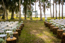 Ceremony setup with our birchwood arch and greens garland, and Babies Breath filled mason jars on stumps.