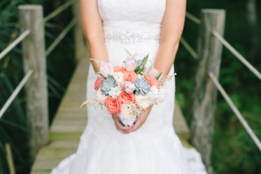 Samantha's bridal bouquet filled with coral roses, blush ranunculus, succuluents, blush astilbe, blush tulips, and white stock.