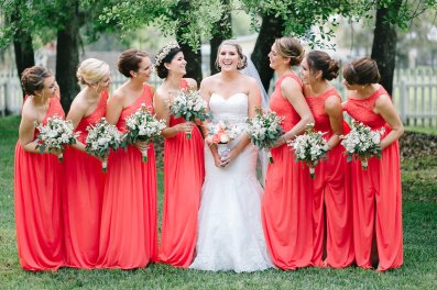 Samantha and her bridesmaid's in coral gowns with bouquets filled with white monte casino, white alstroemeria, white wax flowers, white stock, white veronica, and seeded eucalyptus.