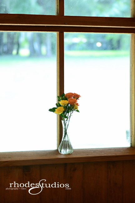 Orange babe spray roses, golden galaxy spray roses, and jade green hypericum in clear bud vases on a window sill.