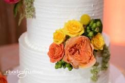Cake floral of jade green hypericum, craspedia, golden galaxy spray roses, orange babe spray roses, green amaranthus, and orange sunset garden roses.