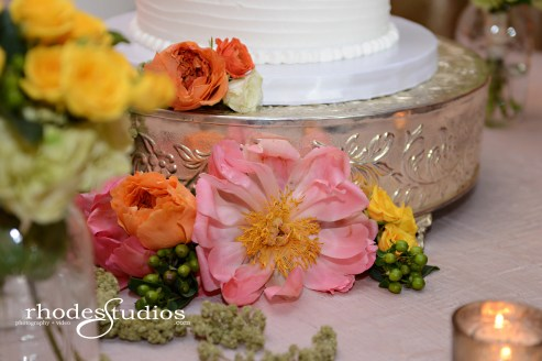 Cake floral of coral charm peonies, jade green hypericum, golden galaxy spray roses, green amaranthus, and orange sunset garden roses.