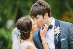 Bride stealing a kiss from her groom.