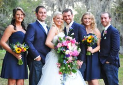 The bridal party showing off the details of their wildflower bouquets. Maids bouquets included ruscus, mini sunflower, pink snapdragons, bright blue delphenium, queens ann, and hot pink spray roses.