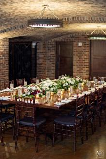 Grand table set for an intimate reception with floral garlands and candlelight.