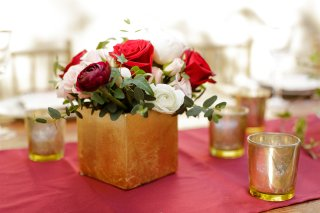 Red roses, greens, white ranunculus, peach spray roses and Juliet Garden Roses.