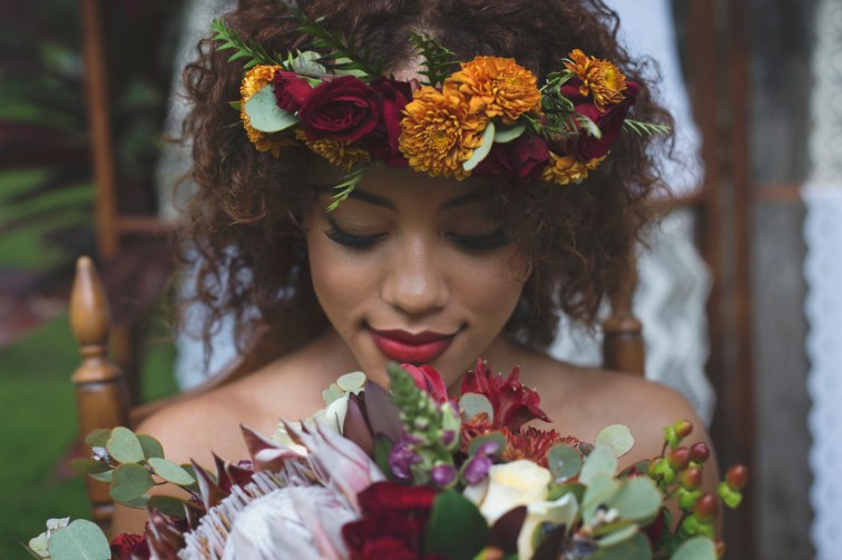 Brides flower halo made of yellow and burgundy mums and bouquet created with yellow and burgundy mums, purple snap dragons, hypericum berries, proteas, ivory standard roses, and greens.