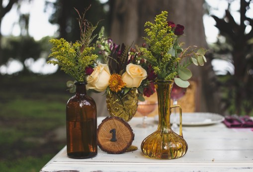 Bud vases with red spray roses, yellow solidago, freedm roses, red alstromeria, hypericum berries, yellow mums, purple snap dragons, greens and ivory standard roses.