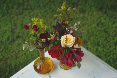 Bud vases with red spray roses, yellow solidago, freedm roses, red alstromeria, hypericum berries, purple snap dragons, greens and ivory standard roses.