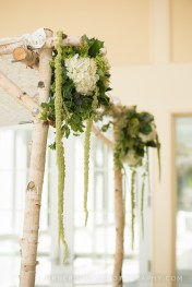 Chuppah arch created with green and white hydrangea, amaranthus, ivy, thistle, and spray roses.