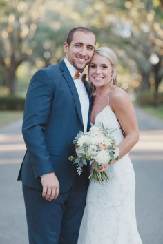 Bride and groom with a peach, ivory and greens bouquet