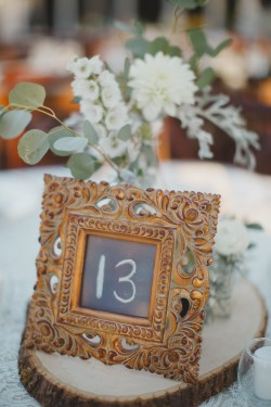 Elegant table numbers on log slices with floral