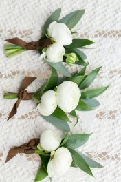 Classic white ranunculus boutonniere with greens and tied off in ribbon.