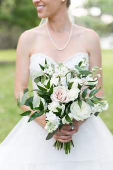 Blush and ivory bridal bouquet with loose eucalyptus and greens for a soft garden feel.