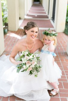 Bride with her flower girl with a blue sash.