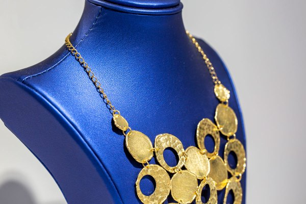 Yellow Gold Circle Bubble Necklace up close angle view on a blue display element.