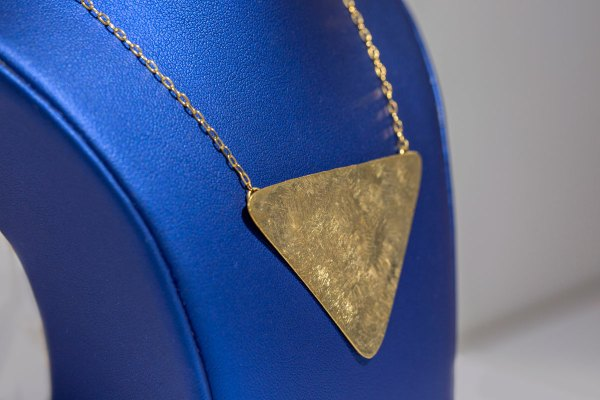 Yellow Gold Triangular Necklace side view on a blue display element.