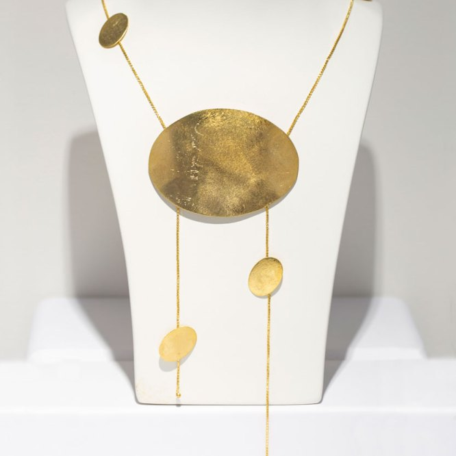 Yellow Gold Floating Ovals Necklace on a white display element.