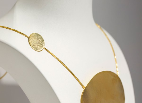 Yellow Gold Floating Ovals Necklace side view up close on a white display element.