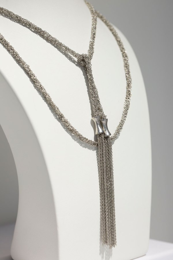 Rhodium Mesh Lariat with Tassels Necklace angle view on a white display element.