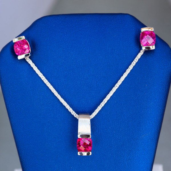 Pink Topaz Pendant and Earrings front view on a blue display element.
