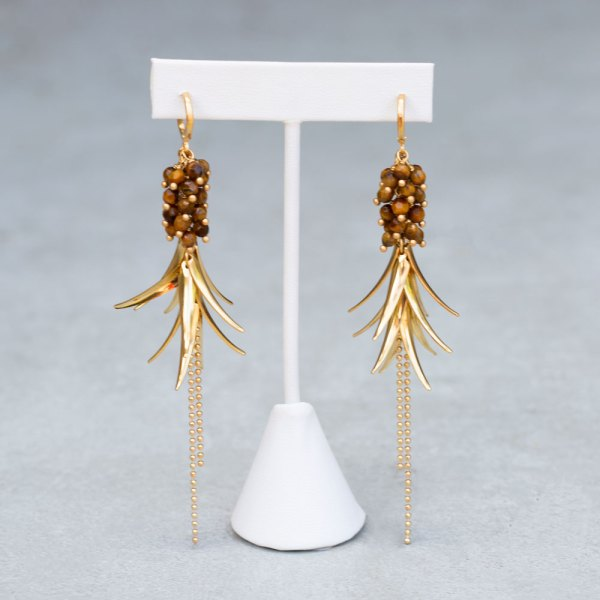 Yellow Gold Overlay Tiger Eye Bead Feather Dangle Earrings front view on a display element.